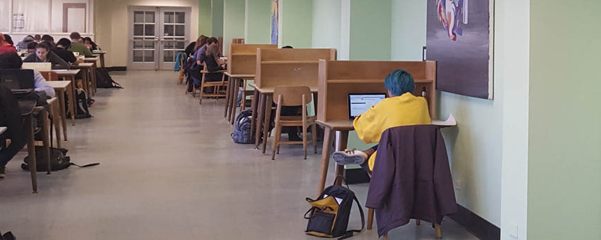 students fill the desks 和 tables in a brightly lit study room