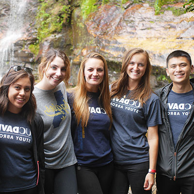 A group of 出国留学 students poses in front of a waterfall